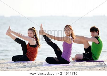 Group of young asian healthy people practicing yoga on the beach healthy lifestyles wellness well being