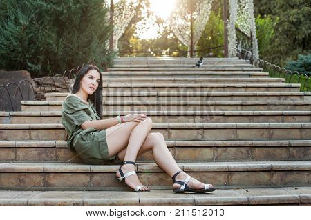 Young attractive woman in green dress sitting on stone steps in nature and thinikg about life. Concept of modern healthy woman
