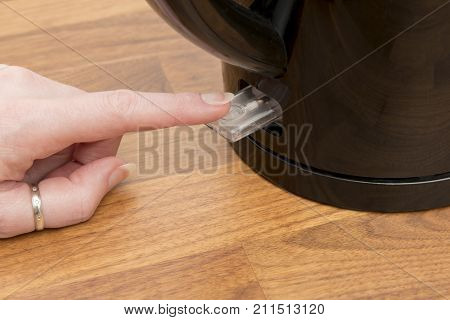 Woman's Finger Pressing The Power Switch Of An Electric Kettle