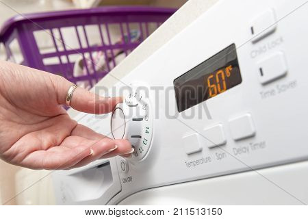 Hand Turning Knob Of Clothes Dryer To Adjust Temperature