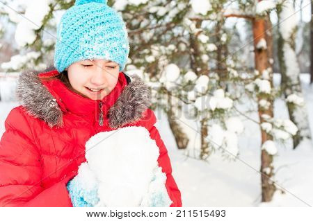 Young cheerful teenage girl inspired of holding soft white snow boll. Bright outdoors horizontal image.