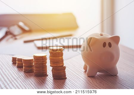 Savings finances economy and home budget calculations. Close up of piggy bank and coins stacked on home desk.