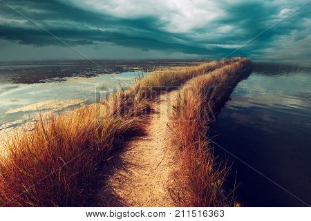 Uncertainty doubt and insecurity in the future. Risky footpath road through water vanishing in distance dark stormy moody clouds bringing bad weather coming towards.