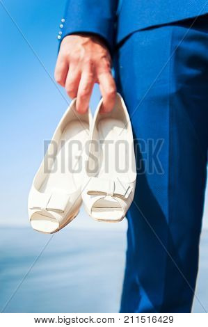 Bridegroom's hand holding woman's white wedding shoes. Vibrant colored summertime outdoors vertical image with filter on blue seascape background. Low point of view.