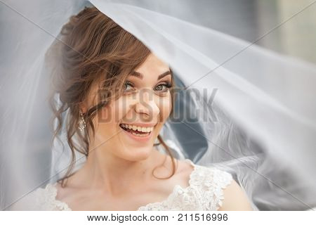 Pretty, young bride laughting with white veil over her face. Concept of young gorgeous bride.