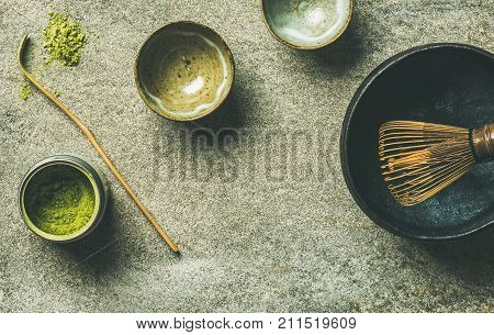 Flat-lay of Japanese tools for brewing matcha green tea. Matcha powder in tin can, Chashaku spoon, Chasen bamboo whisk, Chawan bowl and cups over grey background, top view, copy space