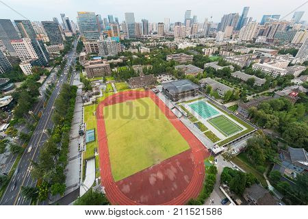 Chengdu, China - Aug 23, 2017 : Huaxi Sichuan University Campus with stadium aerial view and city skyline in the background in Chengdu, Sichuan Province, China