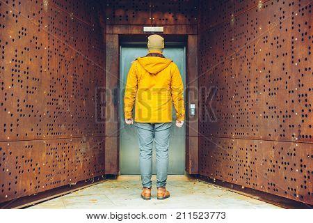 Single Elevator Door outside rusty exterior man wiaitng for elevator