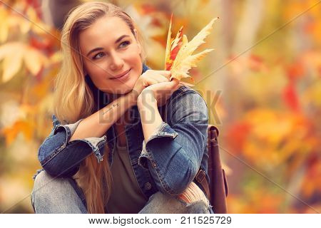 Portrait of a beautiful woman sitting in autumn park with dry maple leaves in hand, enjoying warm weather and beauty of fall nature