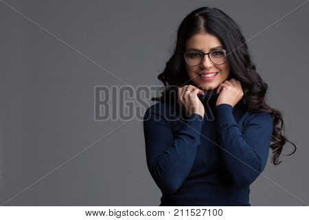 Beautiful blue eyed brunette woman with long curly hair wearing glasses looking directly at the camera and smiling