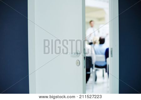 Business seminar or lecture taking place behind slightly open door of boardroom