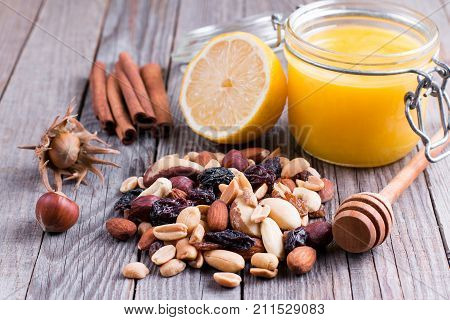 Sweet honey and different nuts on wooden background