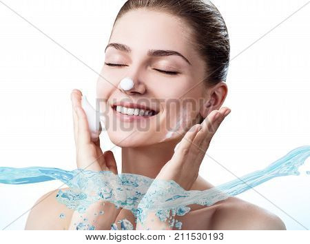 Young sensual woman in wave splashes of clear water. Cleansing and moisturizing concept.