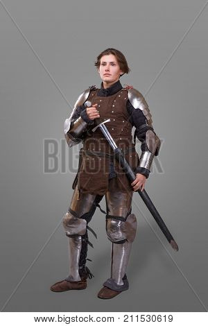 portrait of a medieval female knight in armour with sword isolated over grey background