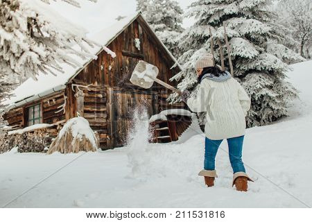 Portrait of a woman with a snow shovel shoveling deep snow in front of a country house