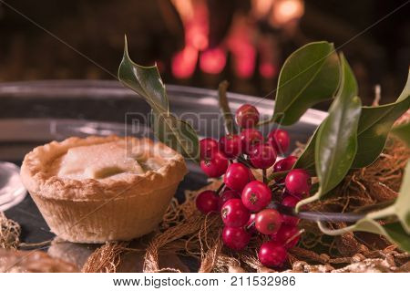 Christmas food and decorations on a silver platter in front of a roaring log fire