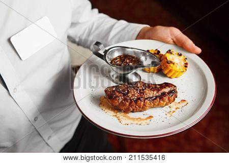 Waiter serve beefsteak with grilled corn and sauce in iron bowl on white plate, closeup view on just prepared juicy meat dish