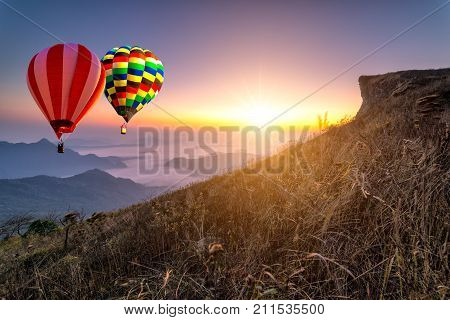 Hot air balloon with tourist is traveling into the peak of mountain and cloudscape at Phu chi fa in Chiangrai Provice Thailand. Beautiful hot air balloon and mist at sunrise. Traveler concept