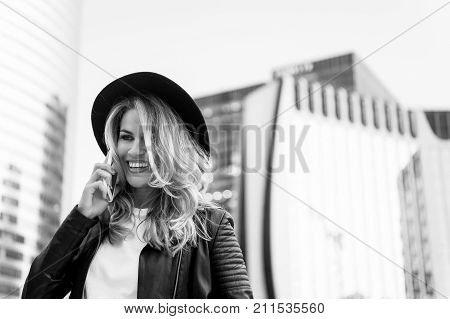 woman with happy face in stylish hat speak on phone. Girl in fashionable leather jacket with cell phone. Beauty look and urban fashion. communication business and new technology black and white