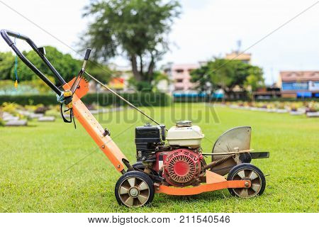 A Man Mowing Grass In The Public Garden. Outdoor Working
