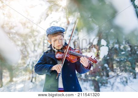 Winter fairy tale. Portrait of cute boy violinist in white winter forest. Playing classic instrument. Dressed in coat. Artistic looking.
