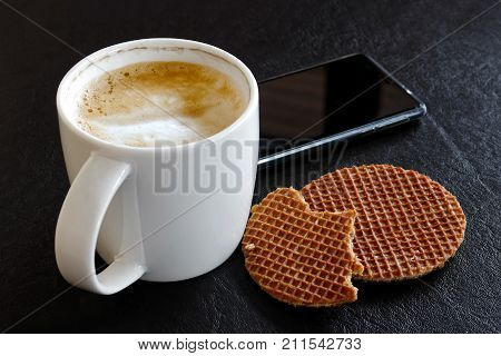 Milky Frothy Coffee In White Mug Partially Drunk Next To Partially Eaten Waffle  Biscuits Isolated O