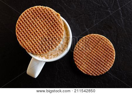 White Mug With Milky Frothy Coffee And A Round Waffle Biscuit On Top Next To Another Waffle Biscuit