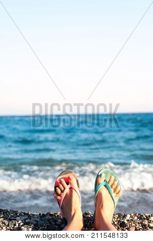 Funny woman feet with multi-colored pedicure in slippers on summer pebble beach background. Inspirational vibrant outdoors vertical close-up image.