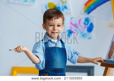 Close-up portrait of cute smiling white three years old boy in blue shirt and jeans apron with brush in the hand. Concept of early childhood education talent happy family or parenting