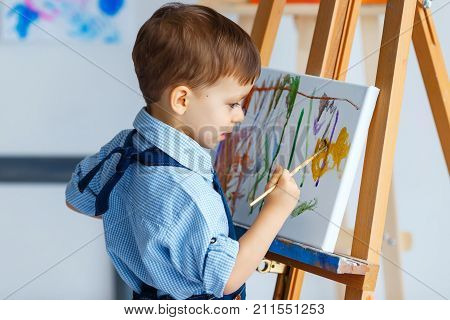 Cute serious and focused white three years old boy in blue shirt and jeans apron drawing on canvas standing on the easel. Concept of early childhood education talent happy family or parenting