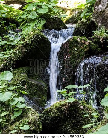 small waterfall with stones covered by moss on Bila Opava river in Jeseniky mountains in Czech republic