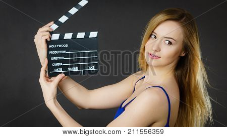 Woman holding professional film slate movie clapper board. Hollywood production objects concept. Studio shot on black background.
