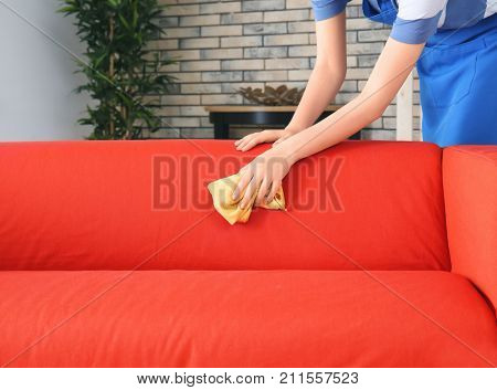Woman cleaning couch with duster at home poster