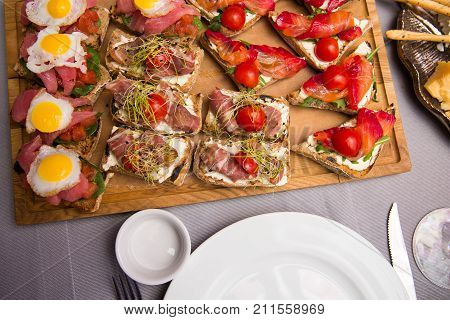 Selection of tasty bruschetta or canapes on taosted baguette and quark cheese topped with smoked salmon meat tomato and chorizo sausage tuna salmon. restaurant feed. New Year Christmas