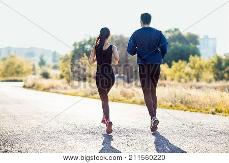 Active Sporty Woman And Man Jogging On Sunny Day
