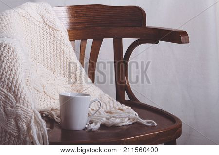 Leisure cozy still life: cup of coffee, super chunky knitting and blanket on vintage wooden chair in living room