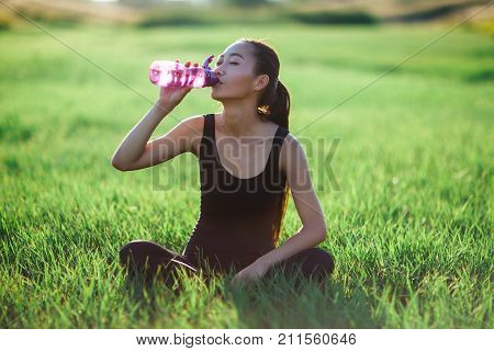 Young Sports Woman On Grass After Jogging Drinks Bottled Water