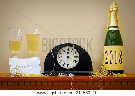 A clock showing midnight at New Year with a bottle of champagne labeled 2018, glasses and invitation surrounded by streamers.