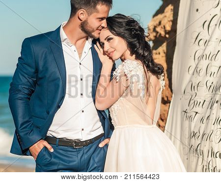 Bride and groom at wedding Day on the beach near the sea. Bridal couple Happy Newlywed woman and man hugging. Bride and groom