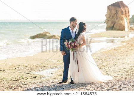 wedding copule. Beautiful bride and groom. Just merried. Close up. Happy bride and groom on their wedding hugging. Groom and Bride on the beach near the sea. wedding dress. Bridal wedding bouquet of flowers