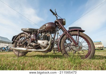 DUNSFOLD, UK - AUGUST 26: Wide-angle closeup of a vintage British Triumph motorcycle at a gathering of classic and modern vehicles in Dunsfold, UK - August 26, 2017