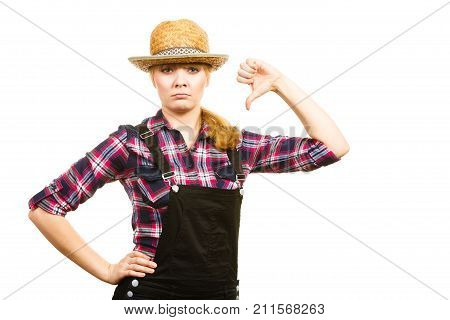 Gardening concept. Attractive woman in dungarees and pink check shirt and sun hat showing thumb down. Isolated background
