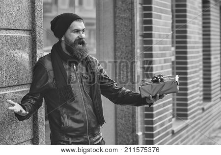 bearded man long beard brutal caucasian hipster with moustache holding blue present or gift box has happy smiling face in black leather jacket hat scarf unshaven guy at building outdoor