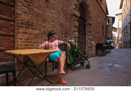The Woman Is Sitting At A Table In The Narrow Street Of Italy.