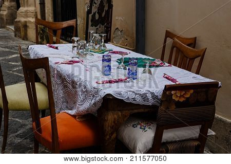 Beautifully served table from tavern on narrow street of Siracuse Sicily Italy
