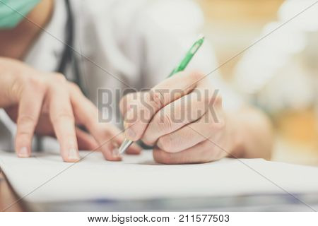 Doctor use a pen writing about healthcare and remedy on paper or prescription document for a healthcare patient in hospital