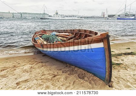 Blue wooden sailing boat with oars at the banks of the Neva in St. Petersburg