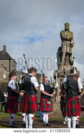 Stirling Scotland - August 17 2010: Band of pipers playing in front of the statue of Robert the Bruce in the Stirling Castle in Sirling Scotland United Kingdom