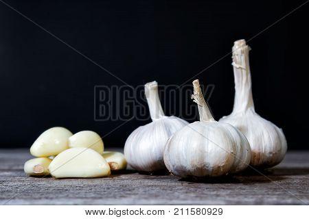 Garlic Cloves and Garlic Bulb. sliced garlic group of garlic on wooden table black background