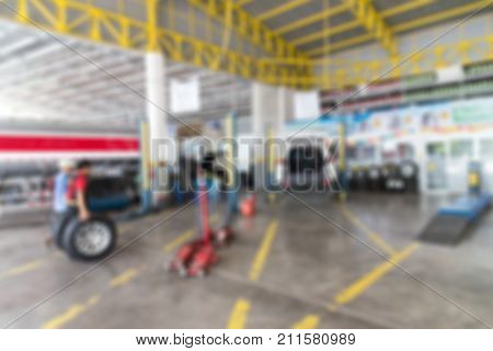 Blurred background of Garage service workshop hydraulic platform elevator.Car technician repairing the car in the garage.